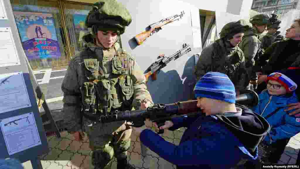 Одетые в форму так называемых зеленых человечков российские военные демонстрировали оружие юным симферопольцам, 23 февраля 2020 года