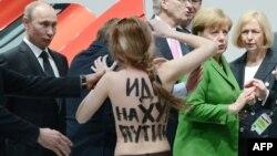 Активистка движения Femen проводит акцию против политики президента России Владимира Путина. Путин - крайний слева. Ганновер, 8 апреля 2013 года.