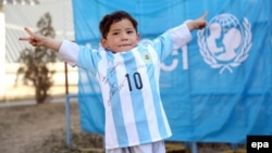 Five-year-old Afghan boy Murtaza Akhmadi, a young fan of FC Barcelona's Argentinian striker Lionel Messi, poses with an Argentinian national soccer team jersey signed by Messi in Kabul on February 25.