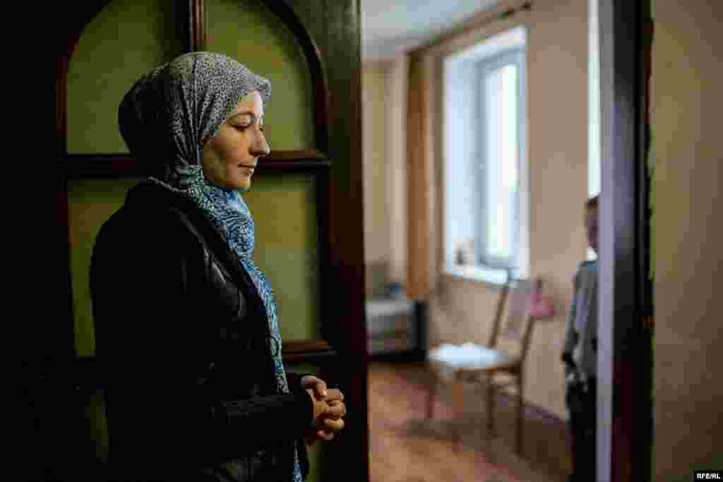 "Miriem stands in her kitchen in Koreiz, Crimea. Her husband, Emir-Usein Kuku, a human rights activist, has been arrested repeatedly in the past year on charges including ""inciting hatred"" or ""denigrating human dignity."""