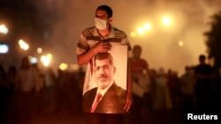 Egypt -- An injured supporter of deposed President Muhammad Morsi carries a poster of Mursi as they run from tear gas fired by riot police during clashes on the Sixth of October Bridge over the Ramsis square area in central Cairo, July 15, 2013