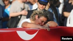 A relative mourns over the coffin holding the body of police officer Nedip Cengiz Eker, killed during the coup attempt, during a funeral ceremony in Marmaris.