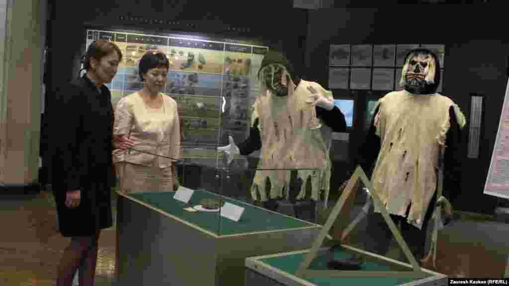 Сотрудница музея Биби Фатима (слева) показывает гостье остатки древнеегипетской мумии, найденные в городе Фивы. Стоящие рядом волонтеры изображают мумии.