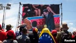 هواداران چاوز، بر پردهای در خیابان، ادای احترام محمود احمدینژاد به رئیسجمهور فقیدشان را تماشا میکنند.