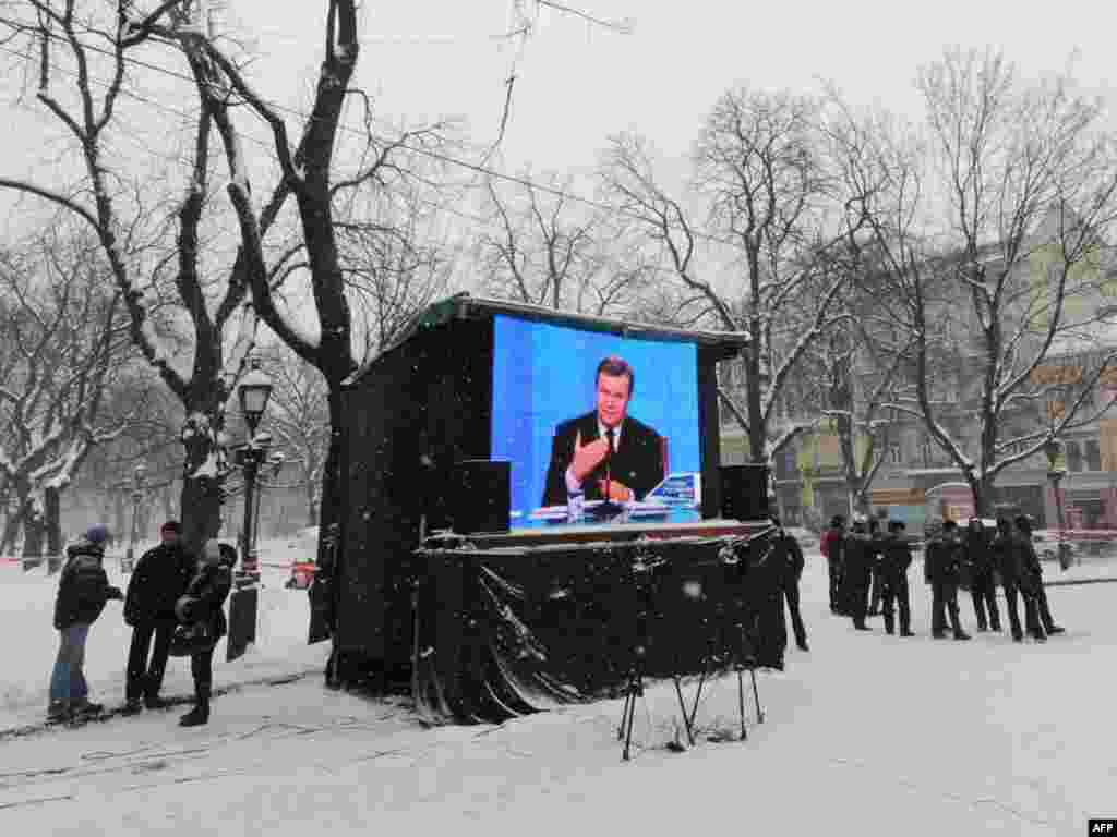 In the center of the western Ukrainian city of Lviv, people ignore a live TV broadcast to mark President Viktor Yanukovych's first year in office. Photo by Yuriy Dyachyshyn for AFP