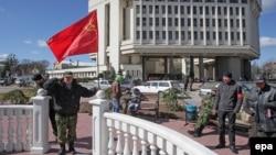 Референдум қорытындысы шыққан соң Қырым парламенті алдында бұрынғы СССР туын ұстап тұрған адам. Симфереполь, 17 наурыз 2014 жыл. (Көрнекі сурет)