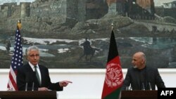 U.S. Secretary of Defense Chuck Hagel (left) gestures while speaking during a joint news conference with Afghan President Ashraf Ghani at the Presidential Palace in Kabul on December 6.