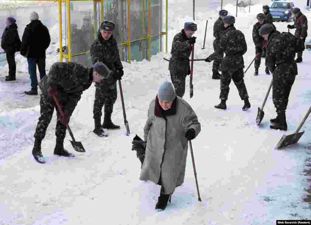A woman walks past soldiers clearing snow and ice from a street after a snowstorm in Kyiv. (Reuters/Gleb Garanich)
