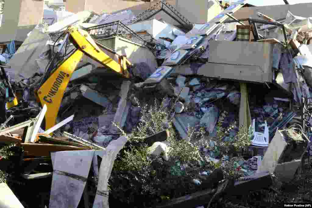 A crumpled building in the Adriatic port city of Durres, 30 kilometers west of the capital, as an excavator works to try to extract survivors.