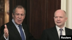 Foreign Minister Sergei Lavrov (L) shows the way to his British counterpart William Hague as they meet in Moscow