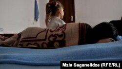 Женщина с ребенком во временном приюте для жертв домашнего насилия.