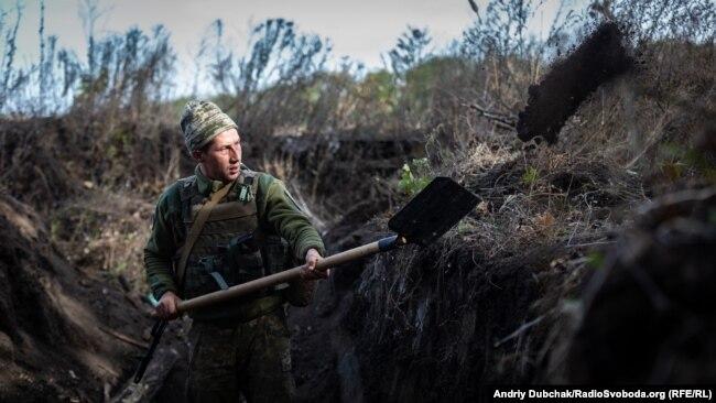 Военный Вооруженных сил Украины копает окоп на новых позициях, рассчитанных на отвод войск в районе Богдановке