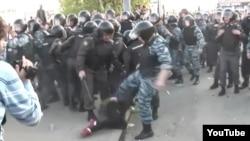 Кадр из видеоролика, на котором сотрудник ОМОНа бьет ногой женщину. 6 мая 2012 года