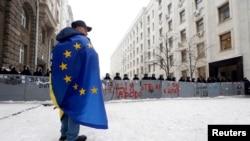 Протестующий сторонник евроинтеграции стоит напротив милиционеров, блокирующих улицу. Киев, 12 декабря 2013 года.