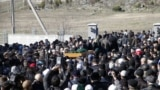 İşğal vaqtında işkencege oğratılıp öldürilgen qırımtatarı Reşat Ametovnıñ cenazesi Aqmescitteki «Abdal» şeer mezarlığında, 2014 senesi martnıñ 18-i. Nümüneviy resim