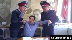 Полицейские задерживают Ермека Нарымбаева. Фото со страницы Андрея Цуканова в социальной сети Facebook. Алматы, 17 октября 2014 года.