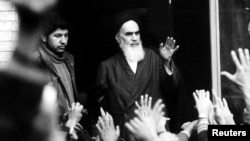 The leader and founder of the Islamic revolution, Ayatollah Ruhollah Khomeini, waves from a Tehran balcony during the country's revolution, in February 1979.