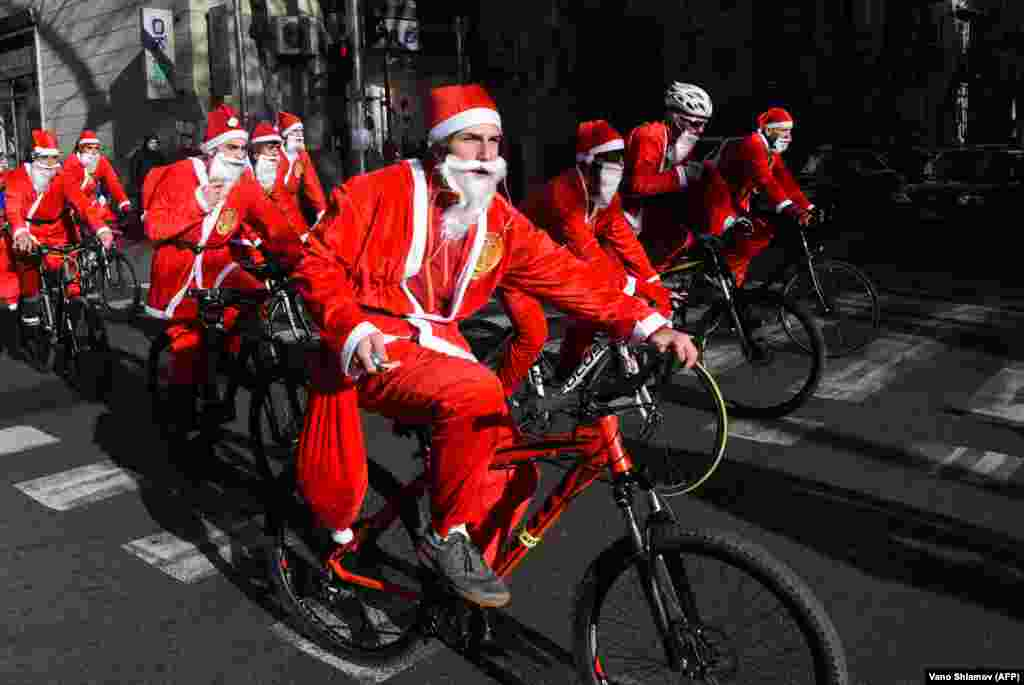 People dressed as Santa Claus ride bicycles through the streets of Tbilisi on December 28. (AFP/Vano Shlamov)