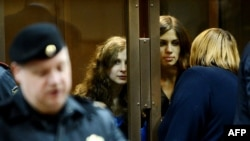 The two members of Pussy Riot whose sentences were upheld, Maria Alyokhina (back left) and Nadezhda Tolokonnikova (back right) speak with a lawyer from a glass-walled cage in a court in Moscow on October 10.