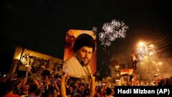 Followers of Shiite cleric Muqtada al-Sadr, seen in the poster, celebrate at Tahrir Square, Baghdad, Iraq, early Monday, May 14, 2018
