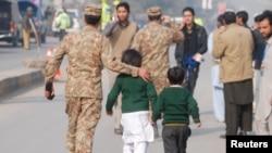 Солдат веде дітей, врятованих зі школи, на яку напали бойовики, 16 грудня 2014 року