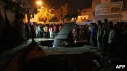 Karachi residents gather around the site of a bomb explosion in that port city in early August.