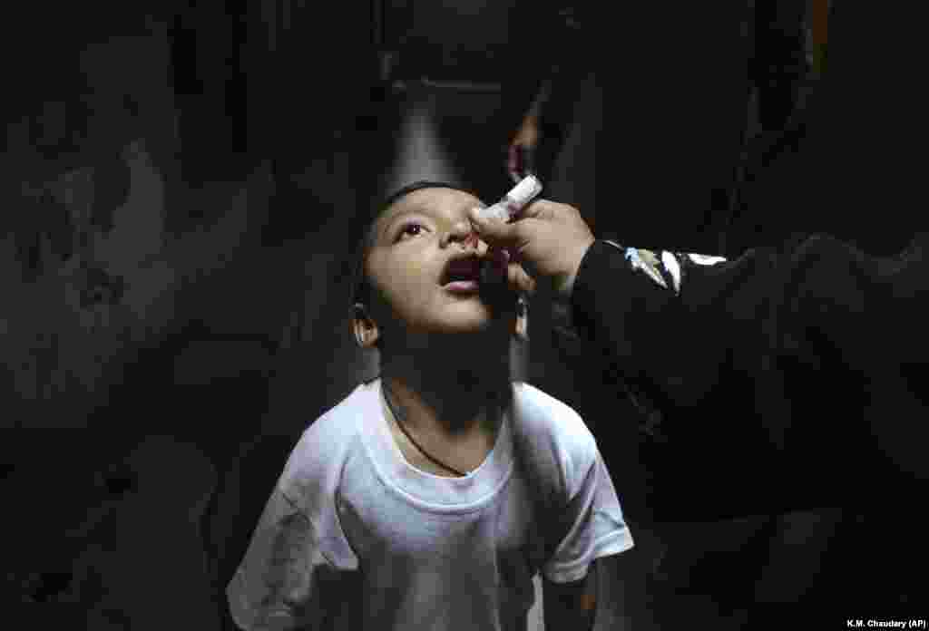 A Pakistani health worker gives a polio vaccine to a child in Lahore. (AP/K.M. Chaudary)