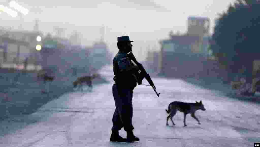 An Afghan police officer secures the road leading to a Kabul guesthouse frequented by foreigners that came under attack by the Taliban. Police said one attacker died when his vehicle detonated and two other militants were killed by police in a gunbattle. One police officer was also killed. (epa/Hedayatullah Amid)
