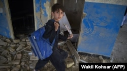 FILE: An Afghan school boy carries his backpack at a school near the site of a Taliban car bomb attack in Kabul in July 2.