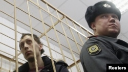 Bolshoi dancer Pavel Dmitrichenko (left) in the dock during a court hearing in Moscow on March 7