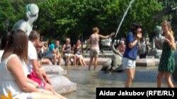 Аптапта фонтандағы суға шомылып жүрген адамдар. (Көрнекі сурет)