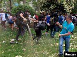Полицейский разбрызгивает слезоточивый газ против демонстрантов в Стамбуле.