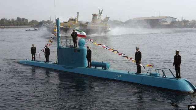 An Iranian Qadir light submarine and a hovercraft  move in Persian Gulf waters in late November.