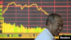 An investor reacts in front of an electronic board showing graph of stock indexes at a brokerage house in Taiyuan, Shanxi province, in July.