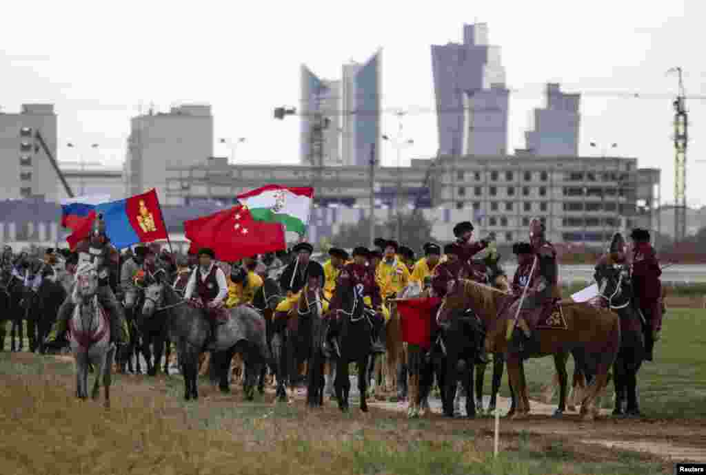 Riders from several of the nine teams competing in the kokpar championships parade on the field during the opening ceremony of the kokpar championship in Astana on September 11, 2013.
