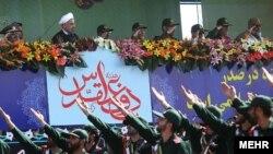 Хасан Рухани (трибунада ак селдечен) Тегерандагы аскерий парадга көз салууда. 22-сентябрь, 2013