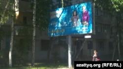 «Халықтық ІРО» бағдарламасы туралы жарнама қасынан өтіп бара жатқан әйел. Алматы, 28 мамыр 2013 жыл.