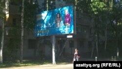 """Женщина идет по улице, где установлен рекламный щит программы """"Народное IPO"""". Алматы, 28 мая 2013 года."""