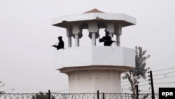 Pakistani police stand guard in the watch tower of central jail in Faisalabad city after government lifted a six-year moratorium on executions.