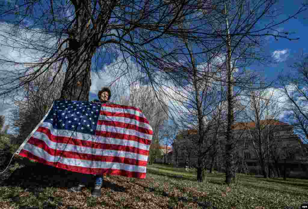 "A supporter holding a U.S. flag waits for the ""Dragoon Ride"" U.S. Army convoy to arrive at a Czech Army barracks in Prague on March 30. (epa/Filip Singer)"