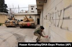 """Турецкий военный пишет слово """"Турция"""" на стене дома в центре сирийского города Африн"""