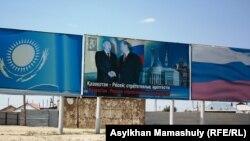 Назарбаев пен Путин қол алысып турған фото плакат ілінген Төретамға кіре беріс жол. Қызылорда облысы, 14 шілде 2013 жыл.