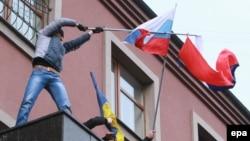 Донецк облыстық прокуратура ғимаратына шығып, Ресей туын көтеріп тұрған адам. 16 наурыз 2014 жыл.