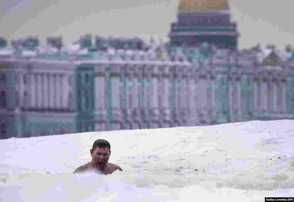 A man swims in an ice hole in the Neva River with St. Isaac's Cathedral and Winter Palace in the background, in St. Petersburg, Russia. (AP/Dmitri Lovetsky)