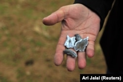 A man holds shrapnel believed to be from a missile launched by Iran on U.S.-led coalition forces on the outskirts of Duhok, Iraq, on January 8.