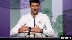 Serbia's Novak Djokovic talks to the press after beating Roger Federer on July 14 to claim his fifth Wimbledon title.