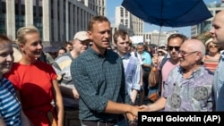 Russian opposition leader Aleksei Navalny (center) shakes hands with people during an opposition rally in Moscow last month against proposed pension reforms.
