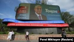 Люди рядом с монитором, на котором транслируют предвыборный ролик президента и кандидата в президенты Казахстана Касым-Жомарта Токаева. Алматы, 3 июня 2019 года.