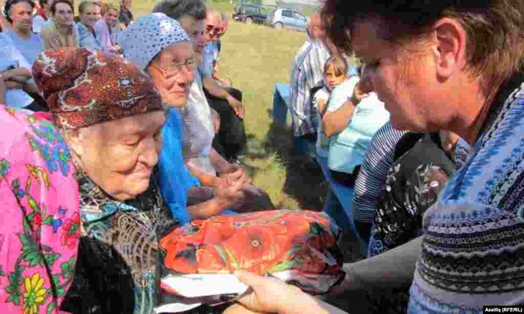 Анна Бровкина 83 яшьлек Рафика Апчалимовага бүләк тапшыра