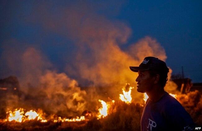 Një burrë shikon zjarrin që ka kapluar fermën ku ai punon. Brazil, 23 gusht, 2019.